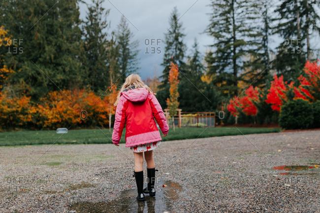 Blonde girl walking through rain puddles