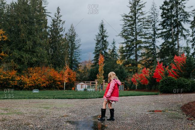 Little girl walking through rain puddles