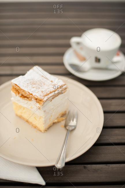Slice of cake on plate near teacup