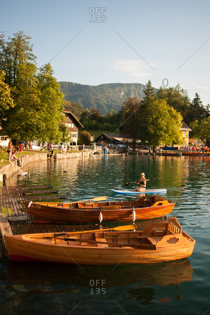 Lake Bled, Slovenia - July 22, 2015: Paddleboarder coming to shore near moored boats on Lake Bled