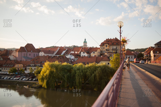 Maribor, Slovenia - July 22, 2015: Man walking dog on The Old Bridge in Maribor, Slovenia
