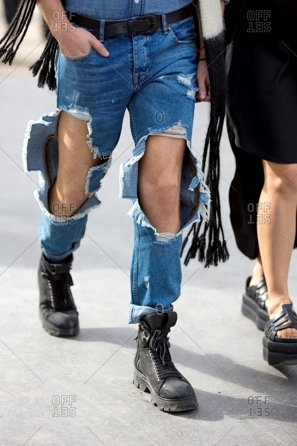 Man wearing jeans with the knees ripped out