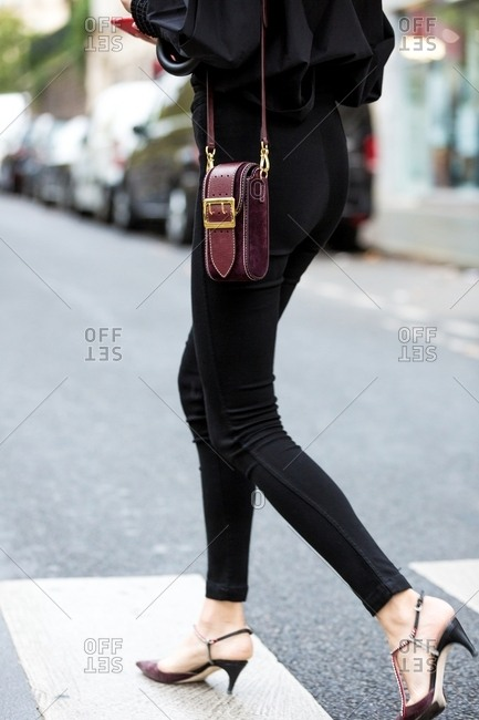 March 14, 2017: Woman with burgundy suede purse and black skinny pants crosses street