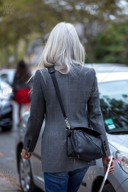 Woman with long gray hair wearing a plaid wool blazer