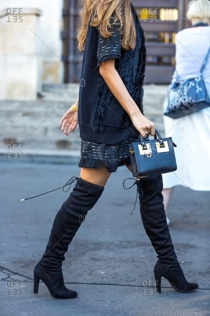Woman in knee-high black boots walking on street