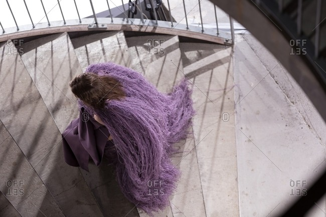 March 14, 2017: Overhead view of woman in purple gown and furry cape walking up stairs