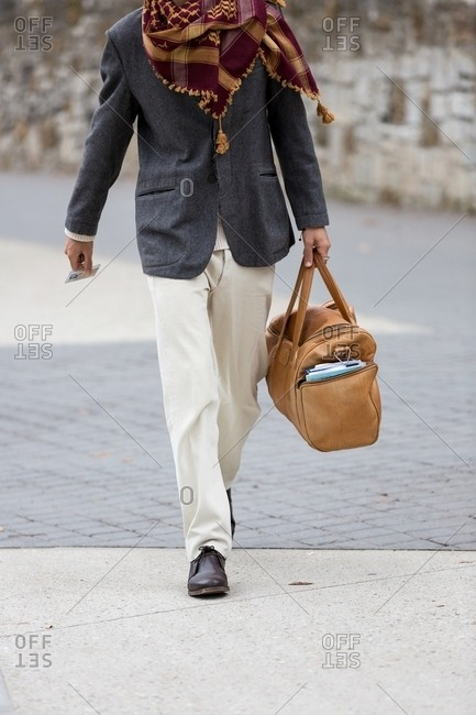 March 14, 2017: Fashionable man with scarf carrying leather duffel bag