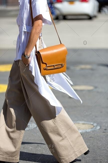 Woman in wide legged khaki pants walking across street