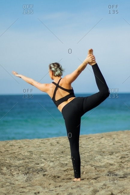 March 14, 2017: Woman doing yoga on the beach