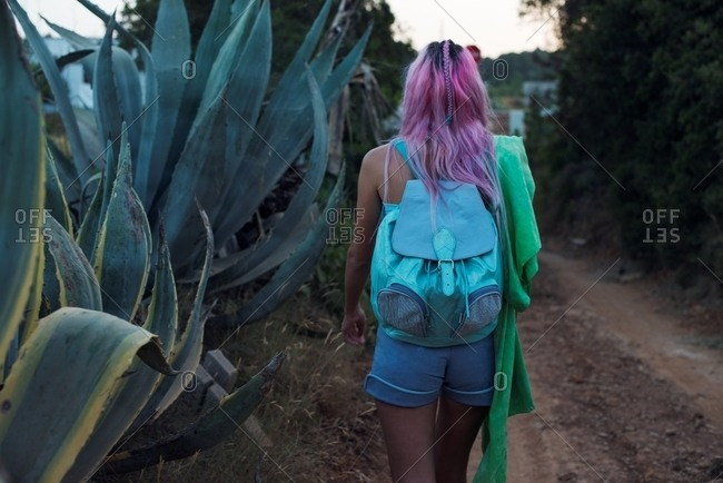 Back view of woman with pink hair walking in desert at dusk