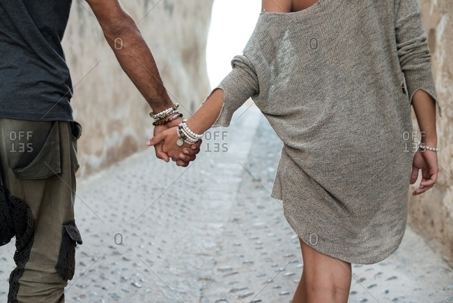 Couple in beaded bracelets hold hands in cobblestone alley