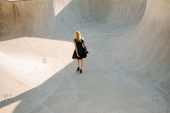 Woman in black dress, walking in concrete skate park