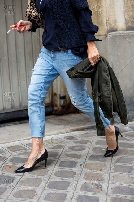 Woman wearing crop jeans and pumps walking down the streets of Paris
