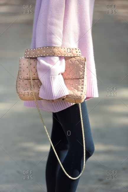 Woman wearing pink sweater with leggings and carrying a large purse