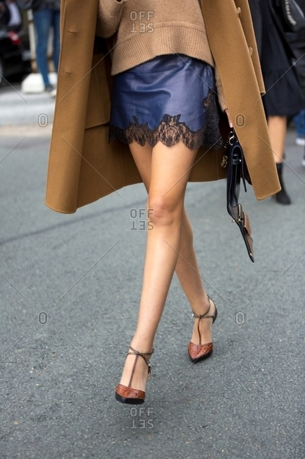 Stylish woman wearing tan coat and heels with blue skirt during Paris Fashion Week
