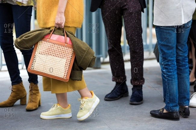 Paris, France - March 14, 2017: Woman at Paris Fashion Week wearing a yellow outfit and holding a wicker bag