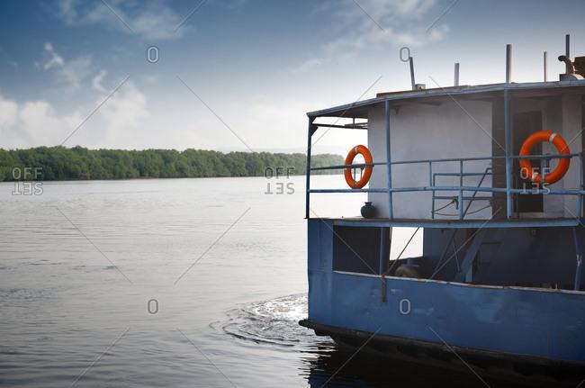 Passenger boat navigating by river, India