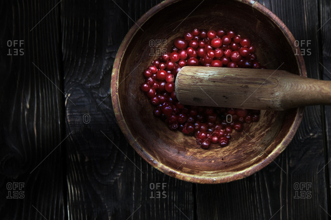 Cranberries in the wooden bowl with pestle