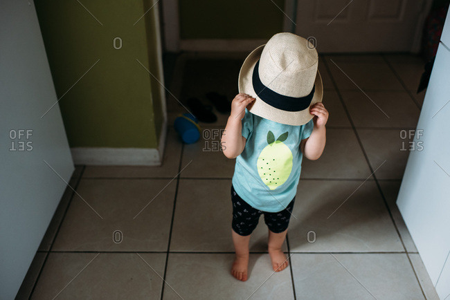 Toddler girl playing with a panama hat at home.