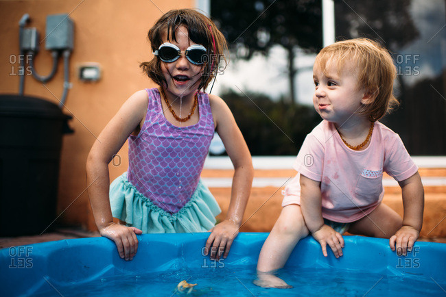 Sisters playing together in a blue kiddie pool on a patio.