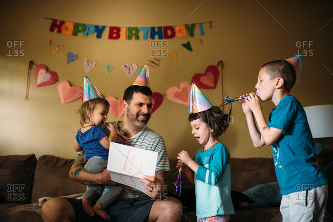 Father opening cards and presents from his kids for his birthday.