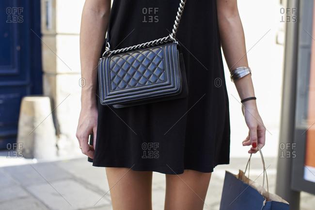 Woman in black minidress with designer handbag, mid section