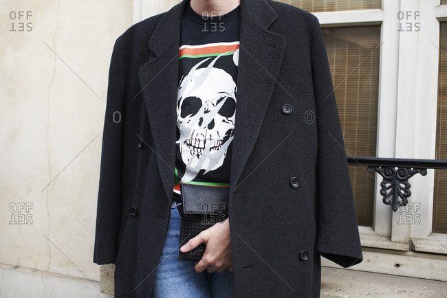 Young adult wearing skull motif t shirt, coat over shoulders