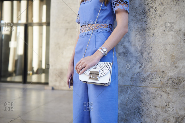 Woman in blue jumpsuit leaning on wall, mid section