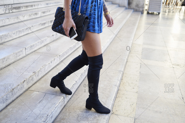 Woman in minidress and thigh high boots walking, low section