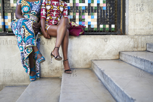 Women in colorful print dresses sitting outside, crop