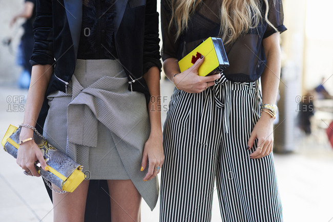 Two fashionable young women holding clutch bags, mid section