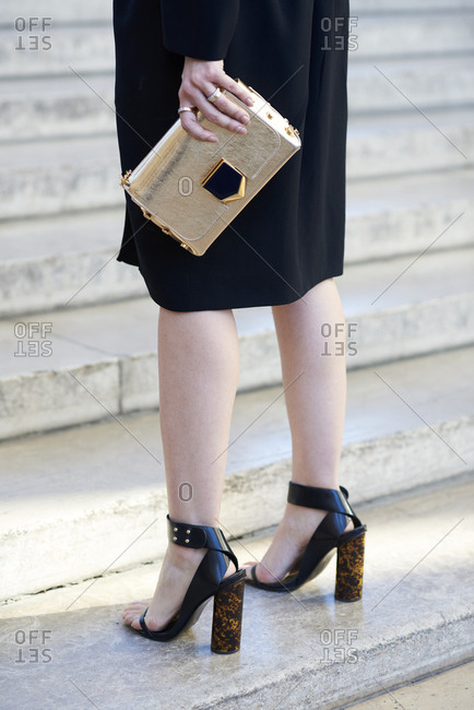 Woman in black dress with gold bag, vertical low section