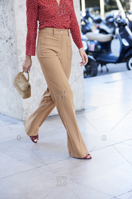 Woman walking in fawn flares and red blouse, vertical crop