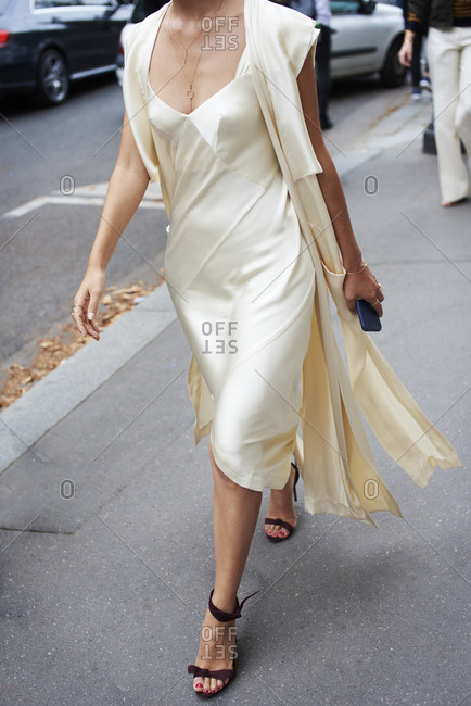 Woman wearing cream silk chemise walking in street, crop