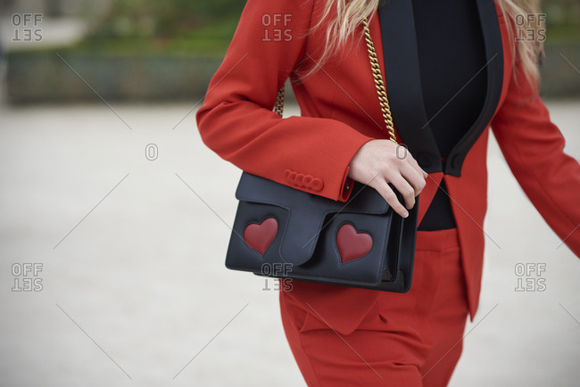Woman in red trouser suit carrying designer bag, mid section