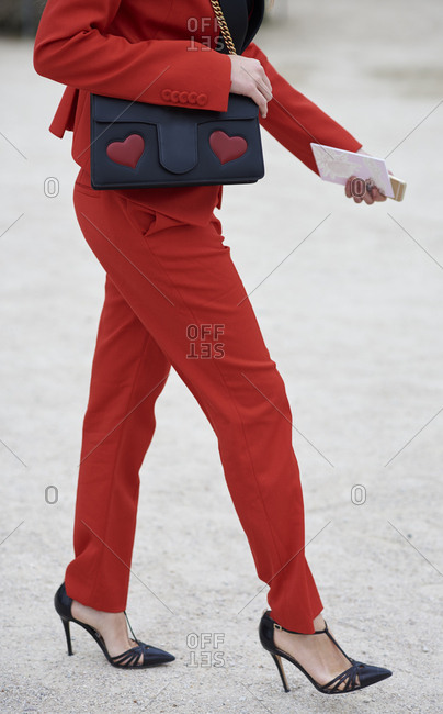 Woman in red trouser suit with designer bag, vertical crop
