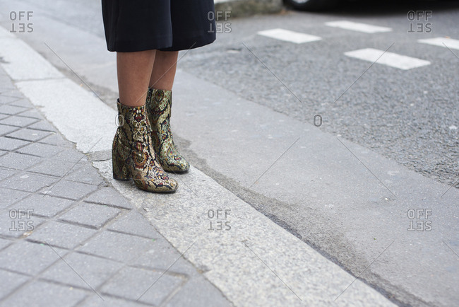 Woman on street in culottes and snakeskin boots, low section