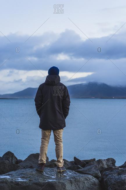 Man standing on ocean front in Reykjavik, Traveling around Iceland, Europe