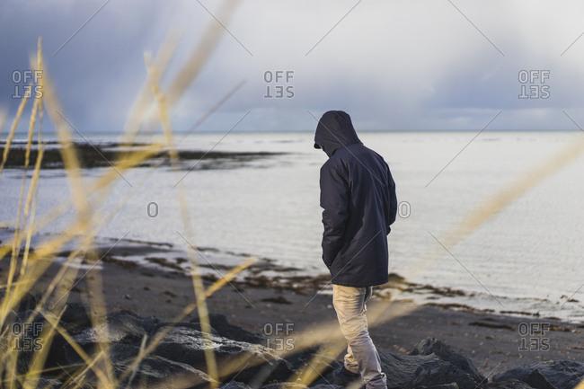 Man traveling around Grotta Island, Seltjarnarnes, Iceland