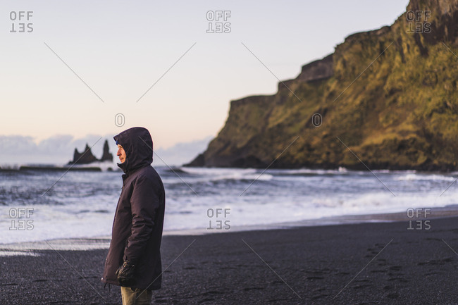 Young traveler watching a sunrise in Vik, Iceland, Europe