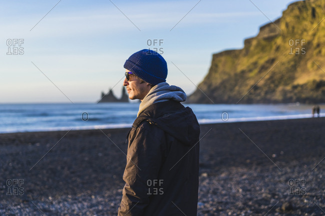 Traveler enjoying sunrise on beach, Vik, Southern Region, Iceland