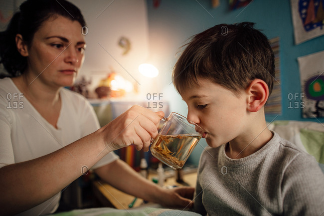 Child feeling unwell drinking a herbal tea from his mother