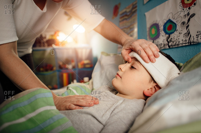 Sick child lying in a bed with a wet cloth on his forehead