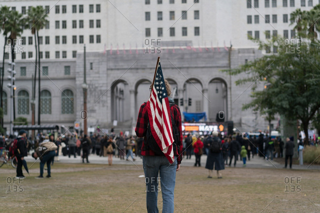 A young man carries an American flag towards a political protest