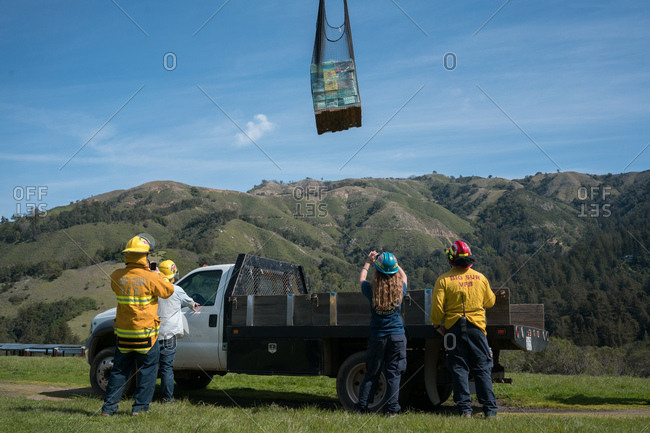 Big Sur, California  - March 3, 2017: Local firefighters and volunteers receive a food drop from a helicopter for the coastal communities surrounding Big Sur that were isolated from severe road damage to Highway 1