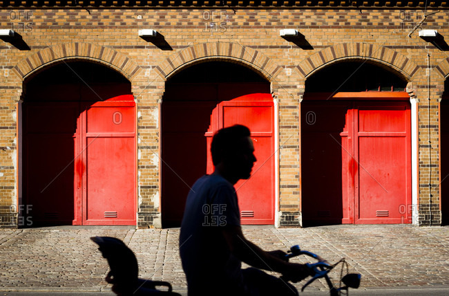 A cyclist passes red doors