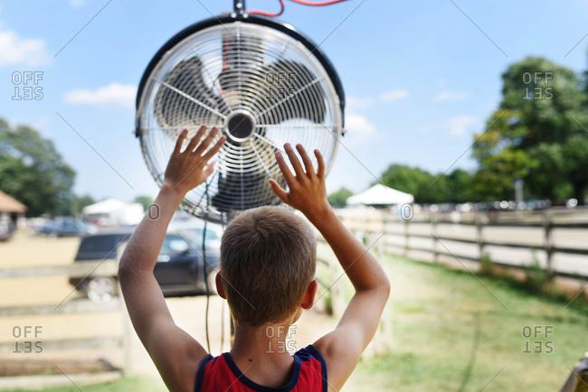 Boy raising hands in front of an outdoor fan