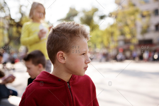 Close up of blonde boy with siblings in background
