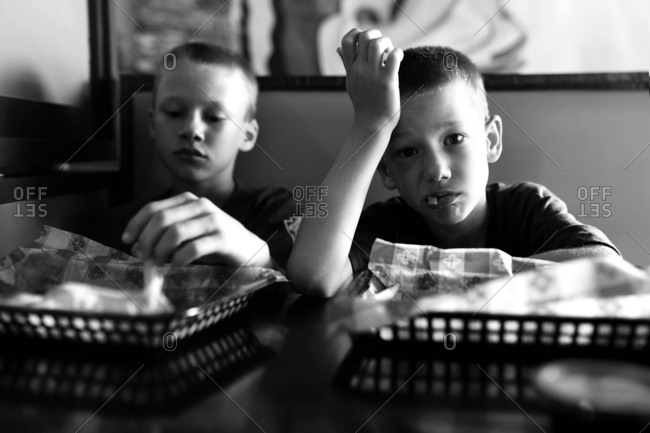 Two boys eating French fries in a restaurant