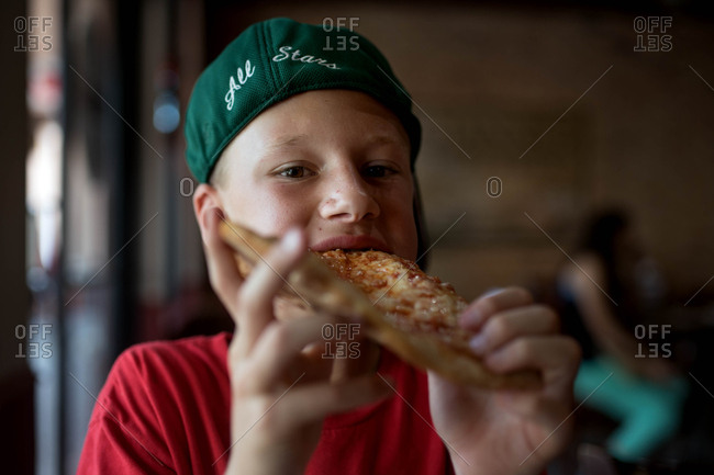Boy eating pizza in a pizzeria